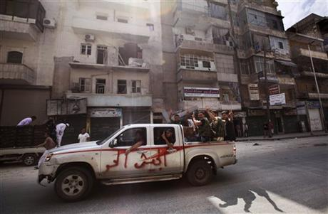 In this Tuesday, Sept. 11, 2012 photo, Syrian rebel fighters flash the victory sign while moving past a building destroyed partly in a government shelling in Aleppo, Syria. Arabic reads on the vehicle,