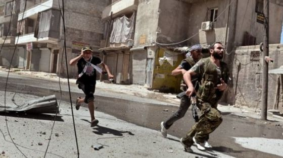 Insurgents run for cover during clashes with Syrian forces in a neighborhood of Aleppo, August 25, 2012.